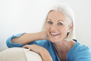 Portrait of cheerful mature woman relaxing on sofa at home