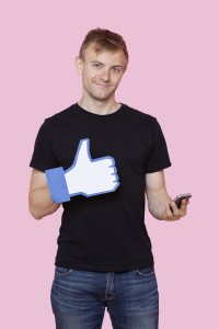 Portrait of a happy young man with cell phone holding fake like button over pink background