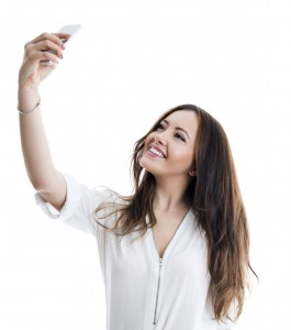 Woman in white shirt with mobile phone taking a selfie. She has a beautiful toothy smile and she is isolated on white.
